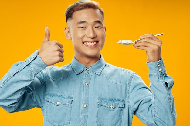 Азиатский мужчина на ярком цветовом пространстве позирует модель, коронавирус