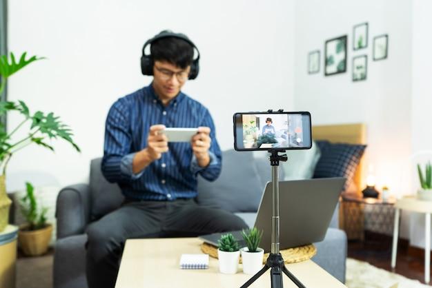 아시아 남자 온라인 인플 루 언서 녹화 비디오 라이브 스트리밍, 디지털 스마트 폰 카메라를 사용하여 소셜 미디어의 카메라 화면 쇼 비디오 블로깅 초점에 대한 테마 제품 리뷰.