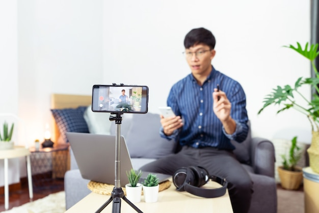 Asian man online influencer recording video live streaming, using digital smartphone camera present product review for theme about video blogging focus on camera screen show on social media.