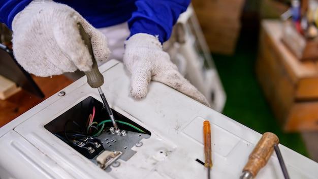 Азиатский мужчина онлайн учится и ремонтирует кондиционер в домашних условиях. новая нормальная жизнь после covid-19. блокировка и самокарантин. оставайся дома и держись на расстоянии.
