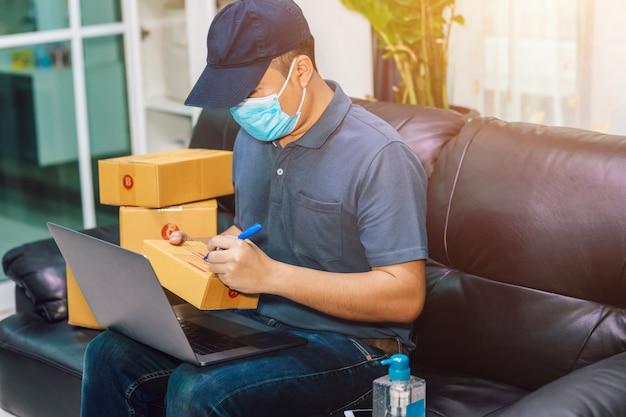Азиатский мужчина онлайн-продаж. продавец готовит коробку доставки для покупателя или электронной коммерции. концепция предотвращения распространения микробов и бактерий и предотвращения заражения коронным вирусом [covid-19]