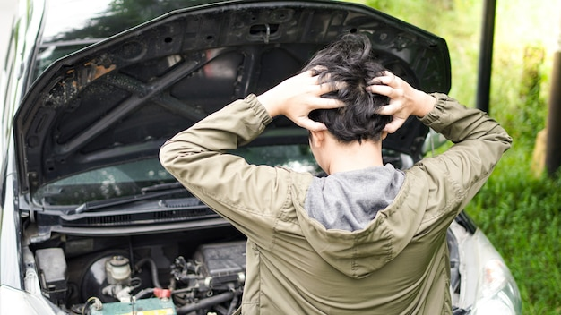Asian man opened the hood of the car while confused