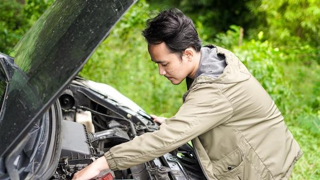 Азиатский мужчина открыл капот и осмотрел машину