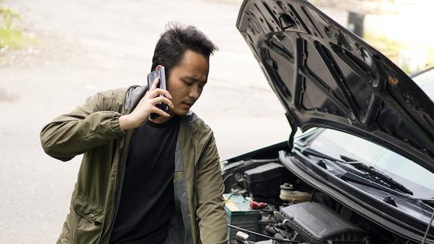 アジア人男性が電話をかけながら車のボンネットを開けた