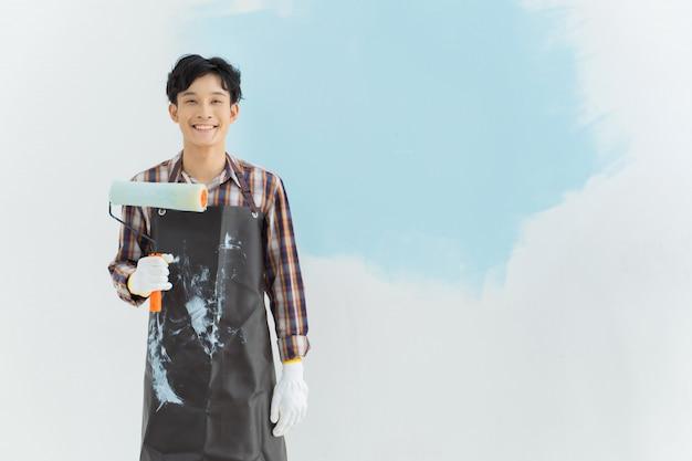 Asian man painting wall at home