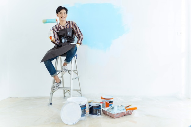 Asian man painting wall at home