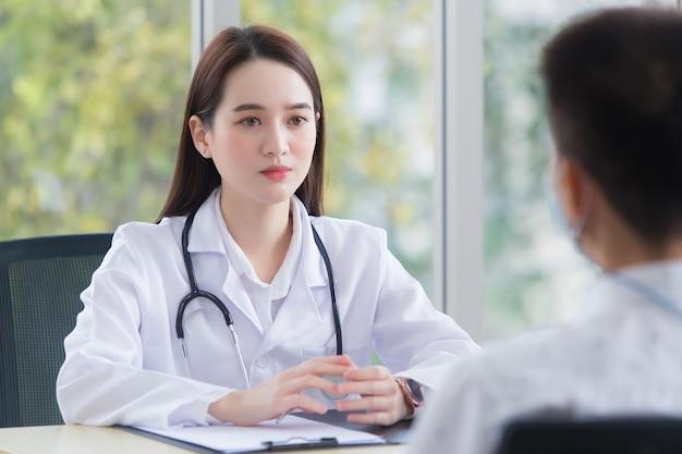 의사가 의료 서비스를 제공하는 동안 아시아 남성 환자는 자신의 증상에 대해 여성 의사와 상담합니다.