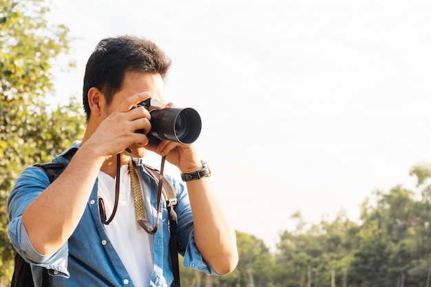 Asian man photographer shooting picture with camera outdoor at park, carer freelancer or leisure activity concept