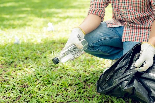 Азиатский мужчина собирает пластиковые бытовые отходы в парке
