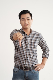 Asian man in plaid shirt and jeans standing in studio with his thumb down
