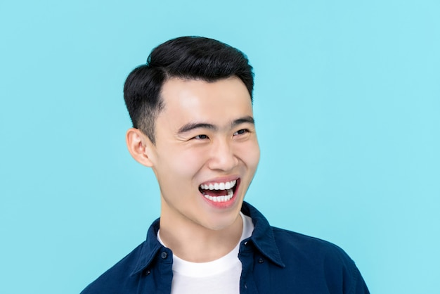 Asian man in plain casual clothes laughing and smiling