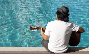 Asian man play guitar on pool water