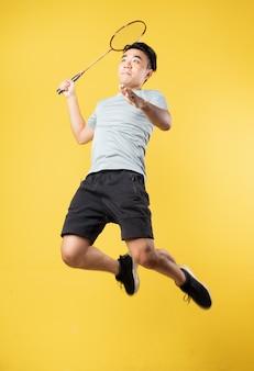 Азиатский мужчина играет в бадминтон на желтой стене