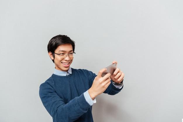 전화에서 재생하는 아시아 남자.