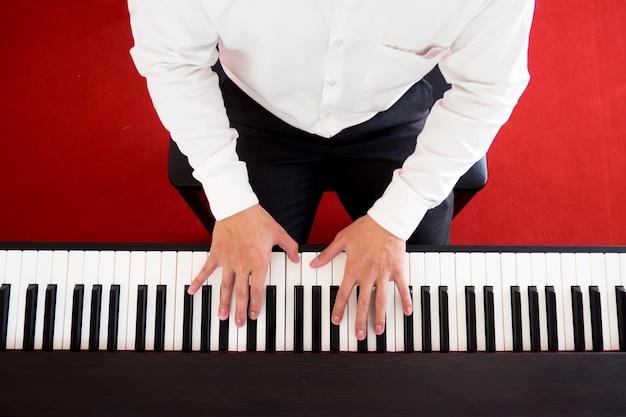 Азиатский человек играет на фортепиано. вид сверху с красным фоном. любимый музыкальный инструмент для изучения базовых навыков ритма и музыки.