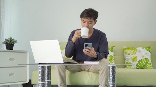家で飲み物を楽しみながらスマートフォンを再生するアジア人男性