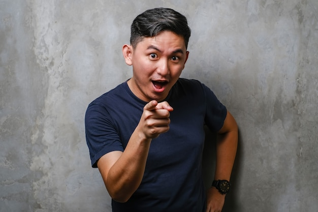 Asian man pointing forward, looking at camera, choosing you over concrete wall background