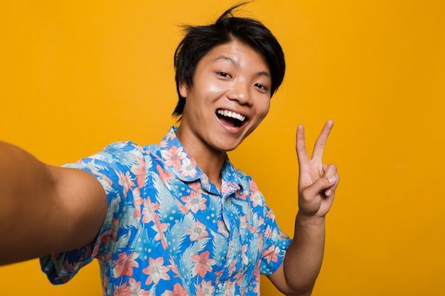Asian man posing isolated over yellow space take a selfie with peace gesture.