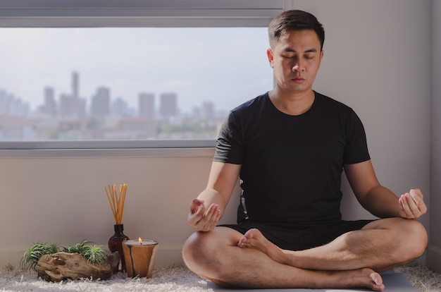 Asian man practicing meditation at home sitting on the floor.