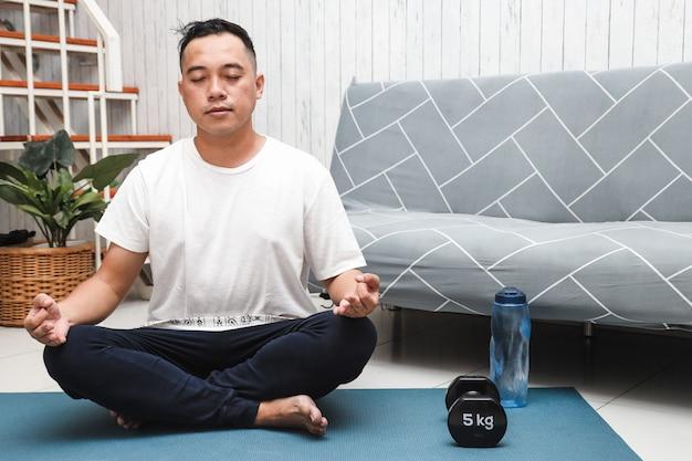 Азиатский мужчина, практикующий йогу или медитацию дома