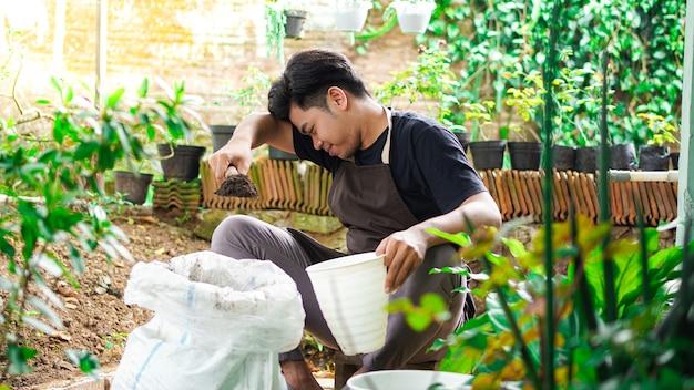 Азиатский мужчина подготовьте место для посадки с горшком и почвой