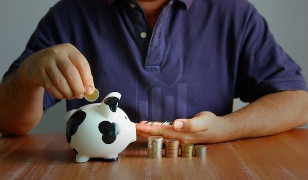 아시아 남자는 동전 쌓기와 추세 그래프를 사용하여 동전을 피기백에 넣습니다. 남자는 저축 옵션으로 재정적 문제를 슬로빙하고 있다