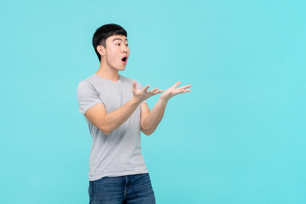 Asian man raising hands with shocked face