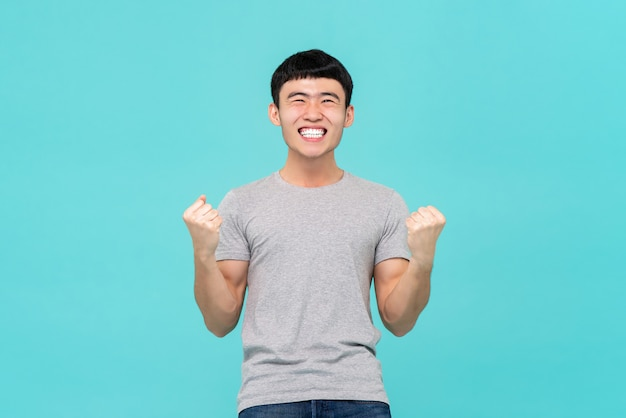 Asian man raising his fists doing yes gesture