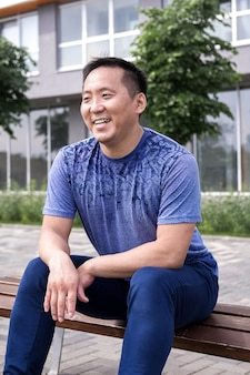 Азиатский мужчина расслабляется после занятий йогой на природе.