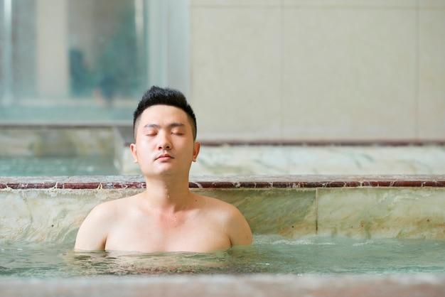 Asian man relaxing in hot tub