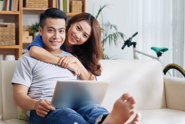 アジア人の男性が自宅でラップトップと彼を抱いて幸せな女性とソファでリラックス