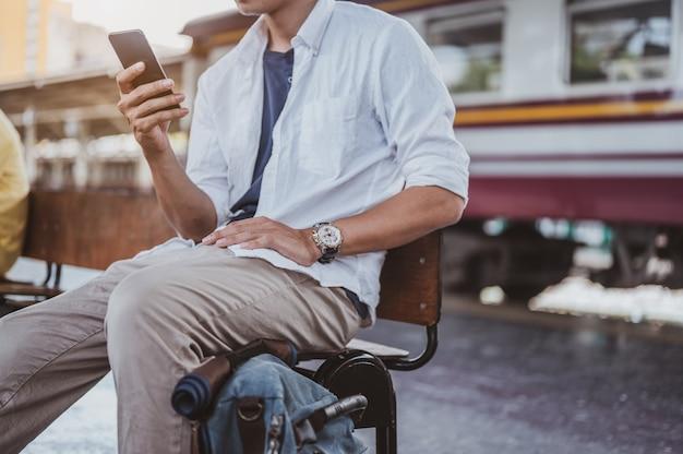 Азиатский мужчина возвращается из отпуска в поездке на поезде, и он использует смартфон, чтобы забрать своих родственников на вокзале. праздник, путешествие, поездка и лето концепция путешествия.