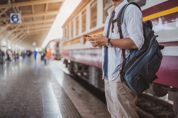 Азиатский мужчина, возвращающийся из отпуска в поездке на поезде, он использует смартфон для своих родственников, чтобы забрать его на вокзале, и он только что сошел с поезда.
