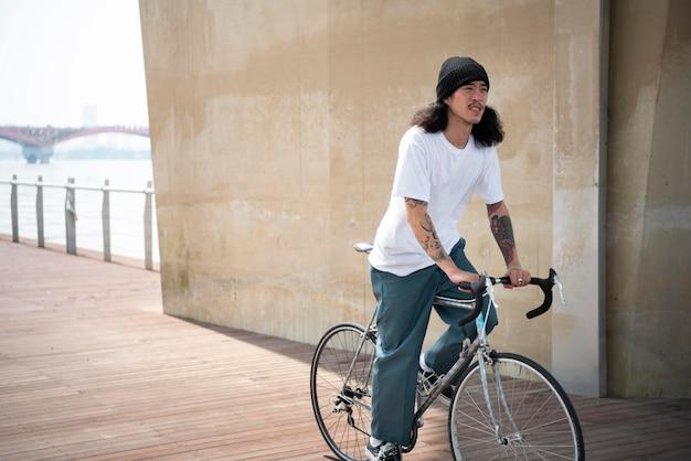 그의 자전거를 타고 아시아 남자