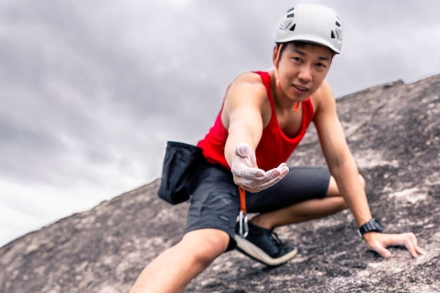 Asian man rock climber in black pants climbing on the cliff and give his hand to help his friend.