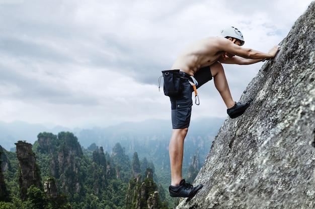 절벽에 등반하는 검은 바지에 아시아 남자 바위 산악인.
