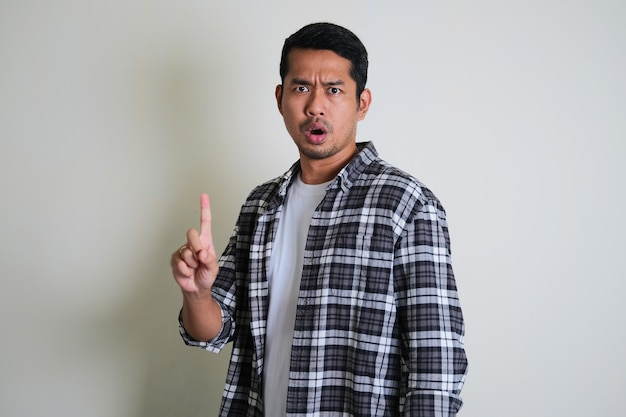 アジア人男性はノーと言い、指サインジェスチャーを与える