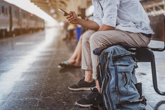 Азиатский мужчина ищет правильное направление на вокзале. путешественник ждет поезд и планирует отпуск со смартфоном. праздник, путешествие, поездка и лето концепция путешествия.