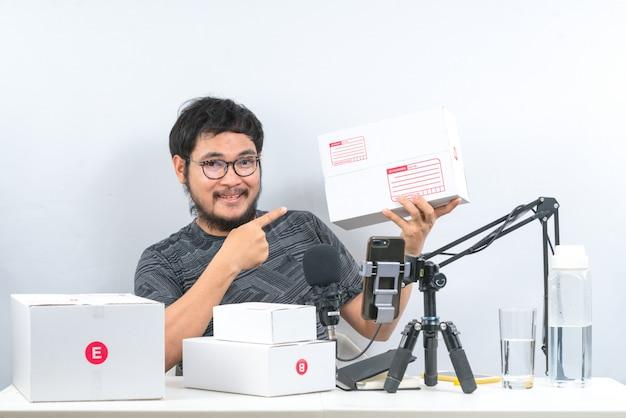 온라인으로 제품을 판매하는 아시아 남자는 주문 구매로 고객에게 배달을 준비하기 위해 양손으로 소포 상자를 들고 있습니다.