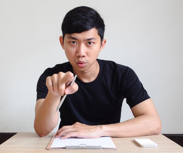 보드와 휴대 전화로 책상에 앉아 아시아 남자 심각한 얼굴 포인트 펜