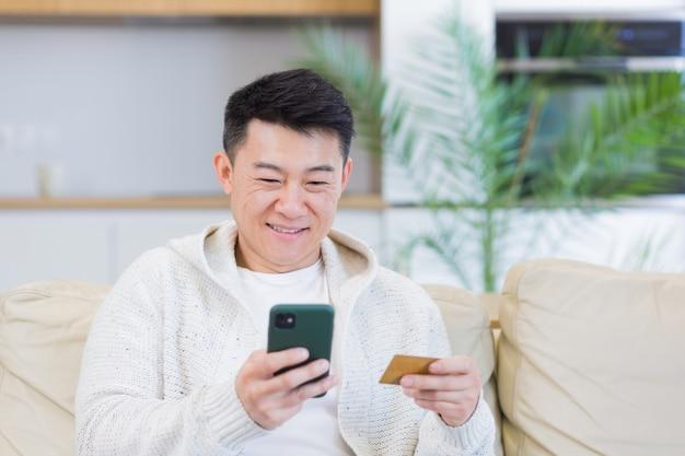 휴대 전화와 신용 카드를 사용하여 인터넷 상점에서 온라인 쇼핑을 하는 아시아 남자