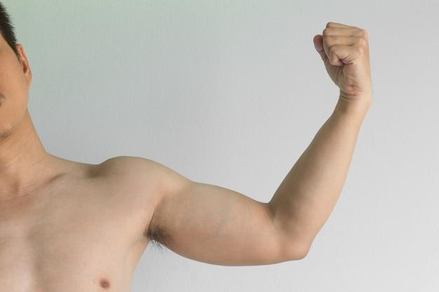 アジアの男性は彼の細い腕を示します
