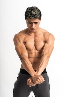 Азиатский мужчина показывает мускулистое тело с двумя руками, вытянутыми вперед