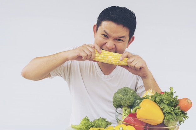 アジア人の男性が新鮮なカラフルな野菜の表情を楽しむ