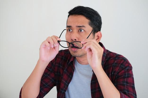 Азиатский мужчина показывает шокированное выражение лица, глядя вперед