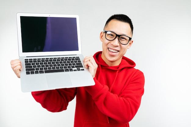 아시아 남자는 흰색 스튜디오 배경 이랑 노트북 화면을 보여줍니다