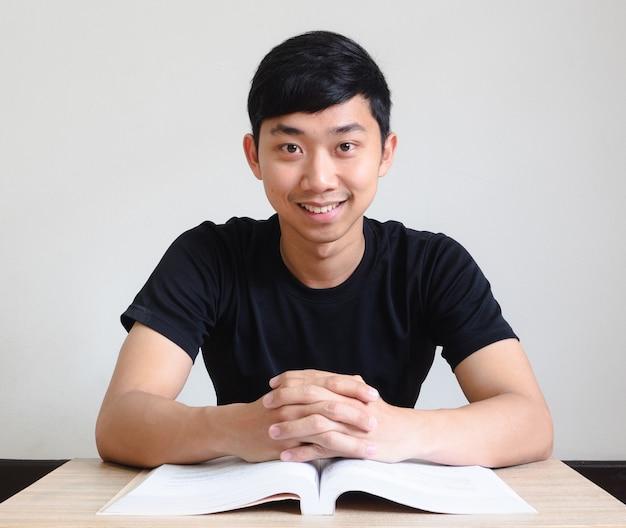 아시아 남자는 업무용 책상에 앉아 있고 책은 행복한 미소를 짓고 있다