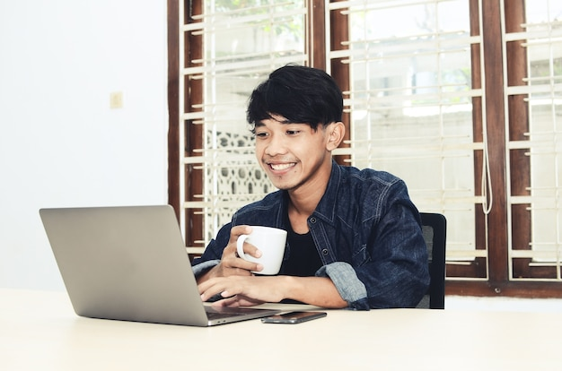 Asian man sits in front of a laptop drinking coffee