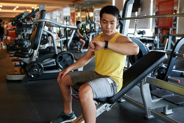 Asian man sitting on bench in gym and looking at wristwatch