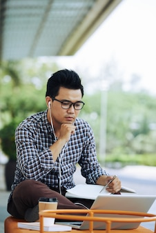 Asian man sitting on bench outdoors with laptop and listening to online webinar